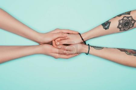 abgeschnittene Aufnahme sinnlicher Frauen, die einander die Hände halten, isoliert auf Türkis