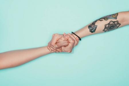Photo pour Photo recadrée de femmes main dans la main isolés sur turquoise - image libre de droit