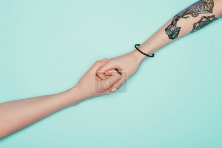 Photo for Cropped shot of women holding hands isolated on turquoise - Royalty Free Image