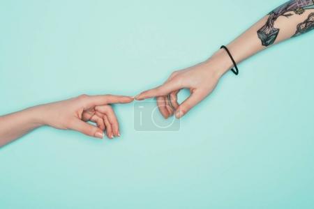 abgeschnittene Aufnahme von Frauen, die Finger isoliert auf Türkis berühren