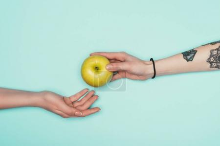 recadrée tir des femmes passant de pommes fraîches isolé sur turquoise