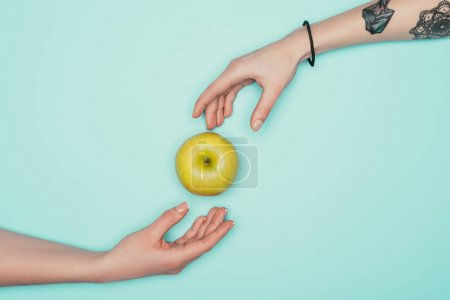 cropped shot of women passing green apple isolated on turquoise