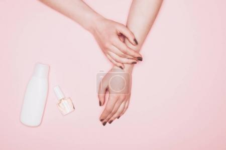 cropped shot of woman with nail polish and bottle of lotion isolated on pink