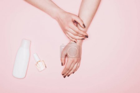 Photo for Cropped shot of woman with nail polish and bottle of lotion isolated on pink - Royalty Free Image