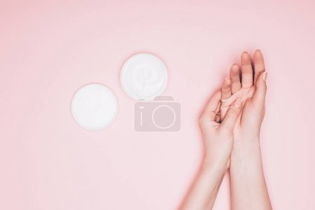 cropped shot of woman applying moisturizing cream on hand isolated on pink