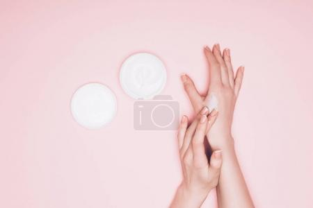cropped shot of woman applying cream on hand isolated on pink