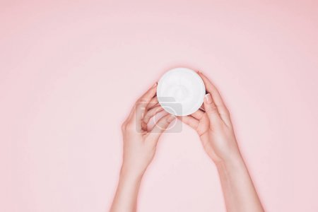 cropped shot of woman holding opened can of moisturizing cream isolated on pink