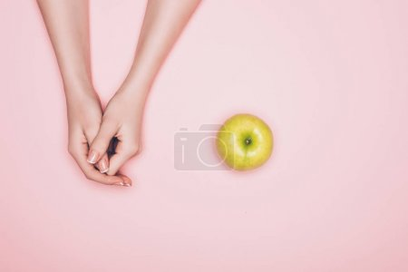 cropped shot of woman with green apple isolated on pink