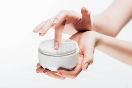 cropped shot of woman taking moisturizing cream from jar isolated on white