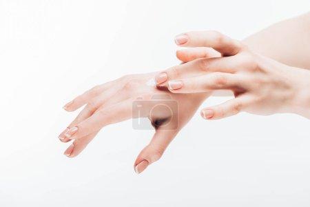 cropped shot of woman applying moisturizing cream on hand isolated on white