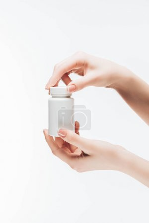 cropped shot of woman holding jar of pills isolated on white