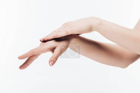 cropped shot of woman applying cosmetic cream on hands isolated on white