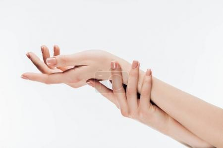 cropped shot of woman with stylish nails applying moisturizing cream on hands isolated on white