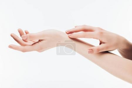 cropped shot of woman applying skincare cream on hands isolated on white