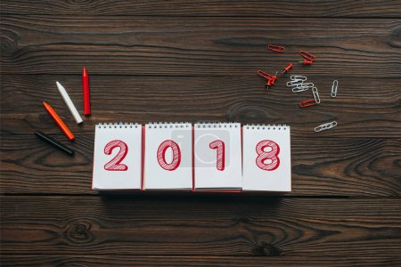 top view of 2018 calendar, pencils and stationery on wooden tabletop
