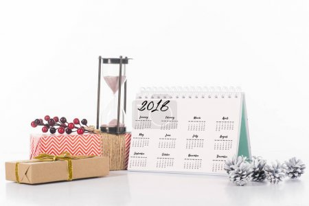 close up view of arrangement of calendar, hourglass and wrapped gifts isolated on white