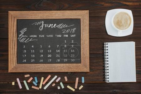 top view of arranged cup of coffee, empty notebook, colorful chalks and chalkboard with june calendar