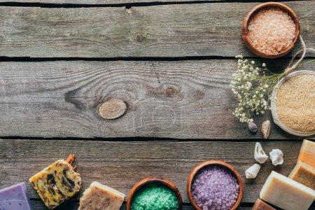 Photo pour Vue de dessus du savon fait maison et du sel de mer dans des bols en bois sur la surface en marbre noir avec espace de copie, concept de spa - image libre de droit