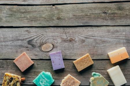 top view of different natural homemade soap on wooden surface