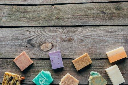 Photo pour Vue de dessus de différents savons naturels faits maison sur la surface en bois - image libre de droit
