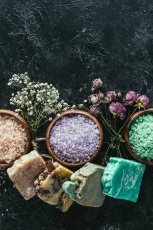 top view of natural soap, dried flowers and sea salt in wooden bowls on black marble surface, spa concept