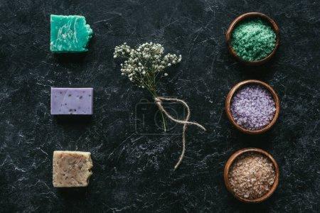 Photo pour Vue de dessus du savon fait maison, fleurs séchées et le sel de la mer sur le concept de spa surface, marbre noir - image libre de droit
