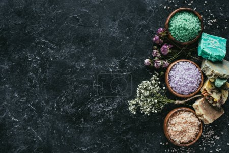 flat lay with homemade soap, dried flowers and sea salt in wooden bowls on black marble surface, spa concept