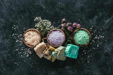 top view of homemade soap, dried flowers and sea salt in wooden bowls on black marble surface