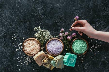 Photo pour Vue recadrée de femelle main avec un savon maison naturel, fleurs séchées et sel de mer pour spa sur une surface en marbre noire - image libre de droit