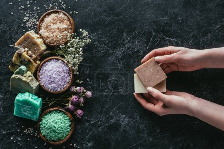 cropped view of female hands with natural homemade soap, dried flowers and sea salt on black marble surface