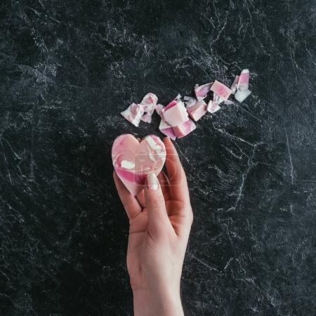 cropped view of female hand with pink heart shaped soap on black marble surface