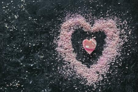 Photo for Top view of pink heart shaped soap and sea salt on black marble surface, spa concept - Royalty Free Image