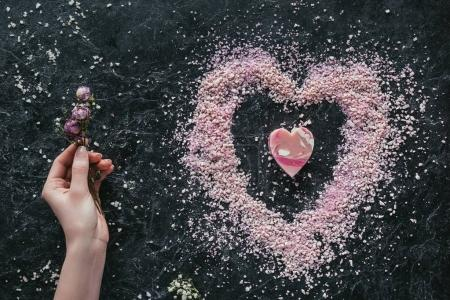 Photo for Cropped view of female hand with dried roses on black marble surface with pink heart shaped soap and sea salt for spa on valentines day - Royalty Free Image
