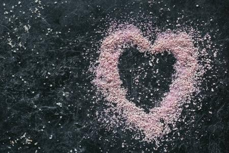 Photo for Top view of heart shaped pink sea salt for spa on black marble surface - Royalty Free Image