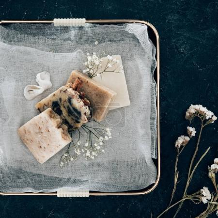 Photo pour Vue de dessus du savon maison naturel et fleurs séchées sur gaze en plateau - image libre de droit