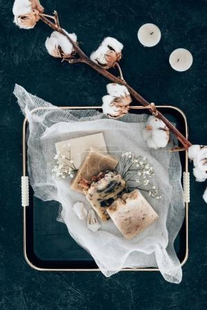 Photo pour Lay plat avec un savon maison naturel et fleurs séchées de coton sur gaze en plateau - image libre de droit