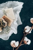 flat lay with natural soap and dried cotton flowers on gauze on marble surface