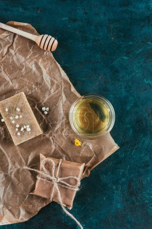 top view of natural soap and oil for spa on crumpled paper on green marble surface
