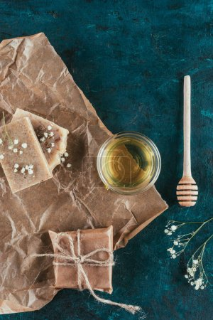 flat lay with natural homemade soap and oil for spa on crumpled paper on green marble surface