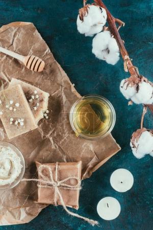 flat lay with natural soap, oil, salt scrub and cotton flower on crumpled paper on green marble surface