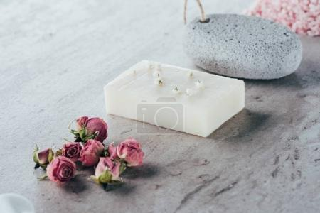 spa treatment, dried roses, natural soap and pumice on marble surface
