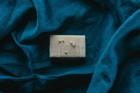 top view of natural homemade soap on dark blue linen