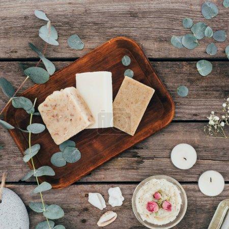 Photo pour Vue de dessus du traitement naturel fait maison de savon, d'eucalyptus et spa sur planche de bois - image libre de droit