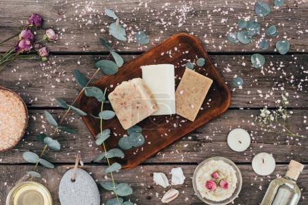 Photo pour Vue de dessus de savon naturel fait maison, eucalyptus, cure thermale et sel sur planche de bois - image libre de droit