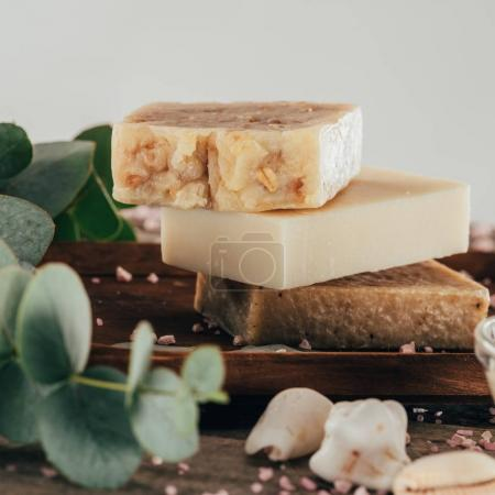 close up of homemade soap and salt for spa on wooden board