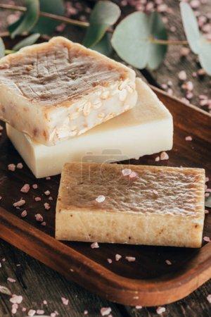 Photo pour Gros plan de savon naturel et de sel pour spa sur planche de bois - image libre de droit