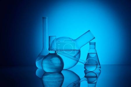 Photo pour Flacons de verre différents sur reflétant la table en laboratoire sur bleu - image libre de droit