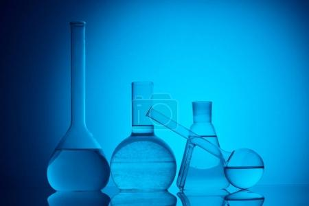 different glass flasks with liquid for chemical test on blue