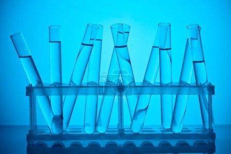 Photo pour Tubes en verre avec du liquide sur le stand de l'analyse scientifique sur bleu - image libre de droit