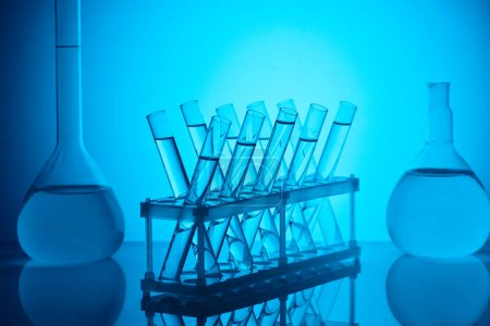glass tubes with liquid on stand and glass flasks on table on blue